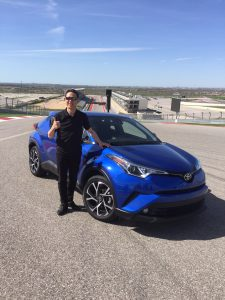 Hiroyuki Koba standing next to his prodigy, the 2018 Toyota C-HR, on a visit to Turn 1 at the Circuit of the Americas racetrack in Austin, Texas.